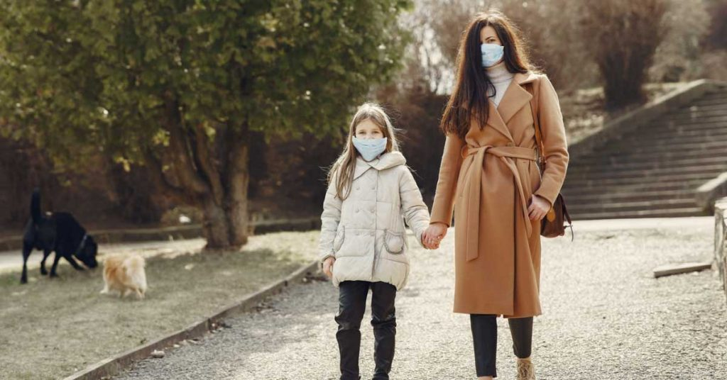 Mother and daughter on a walk wearing masks, while two dogs play in the background