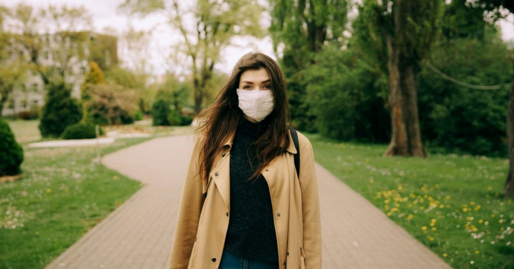 Woman in a brown jacket with a mask on going for a walk