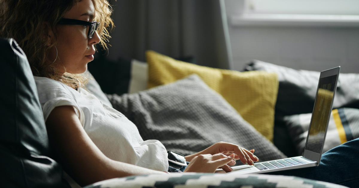 Woman with Glasses sitting in bed working from home on her laptop